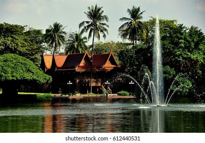 Sampan, Thailand - January 10, 2010:  Wooden Thai pavilion and water jet fountain at the Riverside Rose Garden and Park
