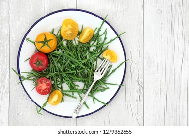 Samphire health food sea vegetable with red and yellow tomatoes on a metal plate with old silver fork, high in antioxidants, fucoidans, dietary fiber and calcium. Salicornia europaea