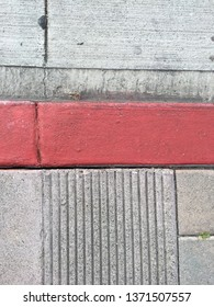 Sample of an emergency curb by serrated concrete and a gutter in a heavily commercialized strip mall parking lot.