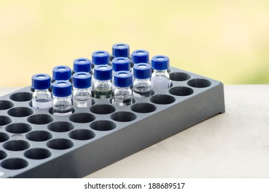 Sample vial in the  instrumental analysis tray on blur green background