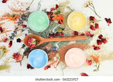 Sampler set preparation of different color clay facial masks in jars, powder and dried herbs scattered, top view skincare ingredients
