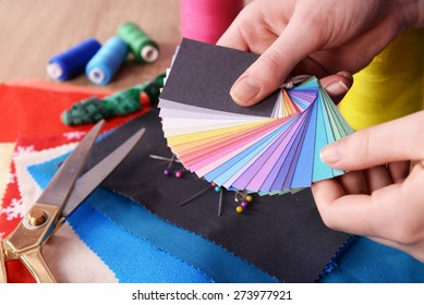 Samples of colorful fabric in female hands, closeup