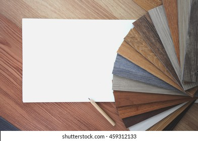 Samples of laminate and vinyl floor tile on wooden Background