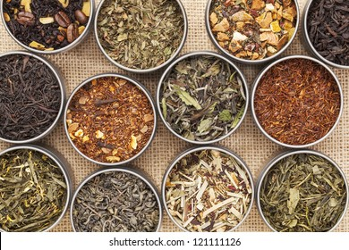 samples of loose leaf green, white, black and herbal tea in metal cans on canvas background
