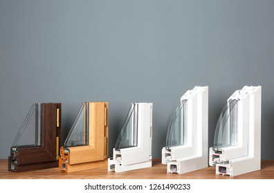 Samples of modern window profiles on table against gray wall. Installation service