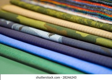 Samples of various, multi-coloured synthetic and cotton fabrics at an exhibition