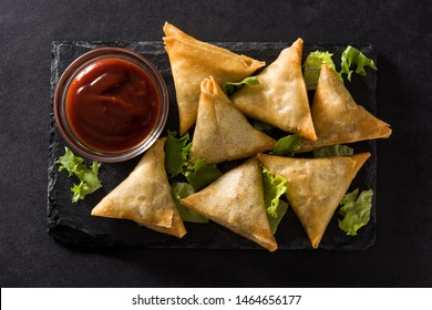 Samsa or samosas with meat and vegetables on black background. Traditional Indian food. Top view.