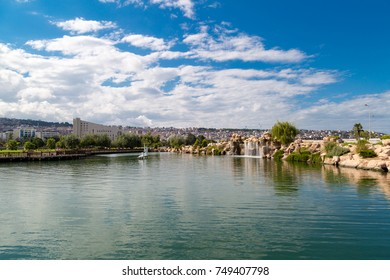 SAMSUN, TURKEY - SEPTEMBER 03, 2016 : General landscape view of small lake with artificial waterfall among bench and seats in natural park on cloudy sky background.