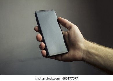 Samsung Galaxy S8 with black screen in hand with grey background