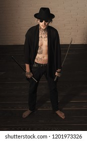 Samurai, buddhist concept. Warrior in black hat and open clothes showing tattooed torso. Man with swords standing on wooden floor barefoot, top view. Harakiri, suicide ritual. Honor and dignity.