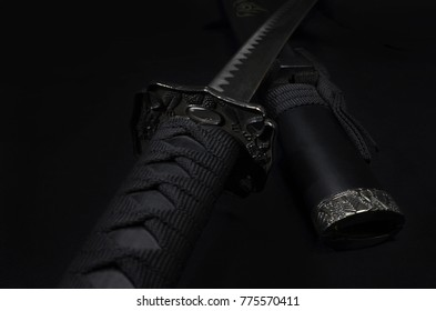 Samurai katana sword laying on black background