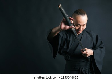 A samurai man in black kimano pulls out his sword on a black background