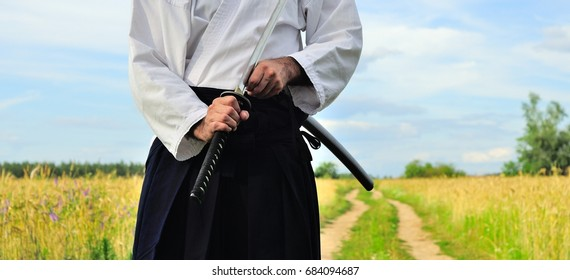 Samurai on the road in the open field. A man in white kimano and black hakame with a samurai sword katana in his hands.