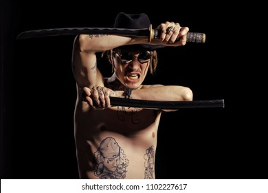 Samurai with sword with tattooed hands, neck and torso shouting aggressive on black background. Defense, honor, torture, punishment, harakiri, tattoo concept.