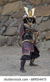 Samurai warrior posing before castle wall in Japan