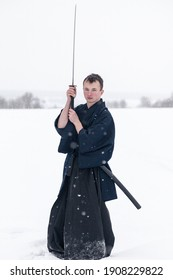 samurai warrior stands with sword and staff in the middle of an empty winter field
