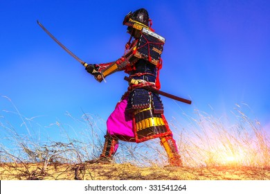 Samurai warrior at sunrise in the field with the sword practices
