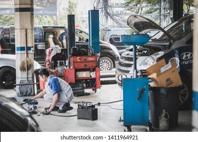 Samut Prakan, Thailand - April, 2019: A mechanic cleaning engine parts at Hyundai service center with Hyundai H1 van parking in the background