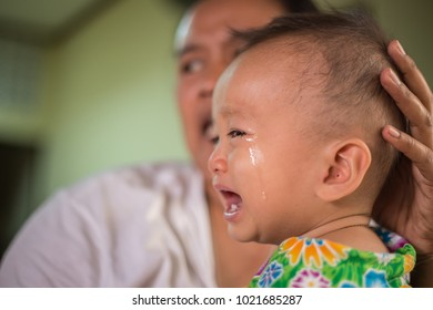 SAMUT PRAKAN, THAILAND - AUGUST 2, 2017: Unidentified Asiatic boy crying in his mother's embrace and comforting little boy crying in public in Samutprakarn.
