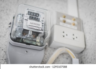 Samut Prakan, Thailand - January 25, 2019: Watt hour meter installed on concrete wall to measure electricity usage with socket to plug in electrical appliances