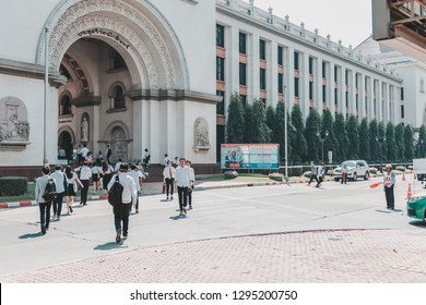 Samut Prakan, Thailand - January 25, 2019: Thai students crossing a road in the campus of Assumption University of Thailand (ABAC)