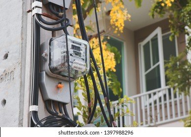 Samut Prakan, Thailand - May 14, 2019: Thai Metropolian Electricity Authority watt hour meter install on electricity pole with house. This meter measure how much the house owner should pay bills