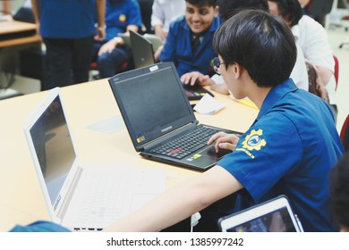 Samut Prakan, Thailand - May, 2019: Portrait of a Computer Engineering student at Assumption University working on his coding project on two laptops