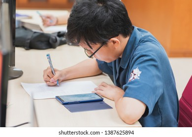 Samut Prakan, Thailand - May 5, 2019: Portrait of Asian university student majoring in computer engineering copying assignments and homeworks questions from his smartphone
