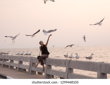 Samut Prakan, Thailand - November 14, 2018: Young woman feeds birds at sunset at Bang Pu seaside-has many migratory birds live therefore there become tourist attractions