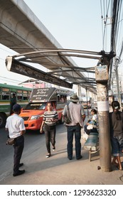 Samut Prakan, Thailand - November 3, 2018: Passengers waiting for the arrival buses under ruined roof of the bus stop, Samrong, Samut Prakan