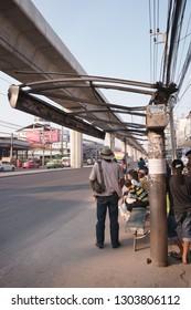 Samut Prakan, Thailand - November 3, 2018: Passengers waiting for buses under ruined roof of the bus stop, Samrong, Samut Prakan