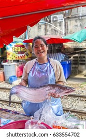 Samut Sakhon, Thailand April 21, 2014 ; Smiling Asian (Thai) woman fish seller in Mahachai fresh market (Maeklong Railway Market) holding smiling hugh fish