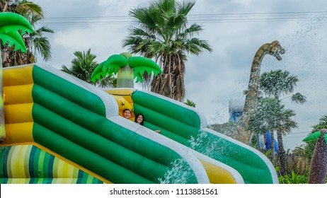 SAMUT SAKHON, THAILAND - APRIL 7, 2018: People having fun on the water slide with friends and family on April 7, 2018 at Pantai Norasingh Water park.