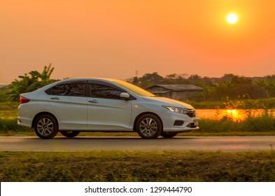 Samut Sakhon, Thailand - Jan, 2019: White HONDA CITY, Motion image, car running on the road with the sunset background, at Samut Sakhon Province on 27 January 2019 in Samut Sakhon, Thailand.