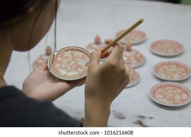 SAMUT SAKHON (THAILAND) Urai Benjarong, An artist decorating a piece of porcelain on a turning table