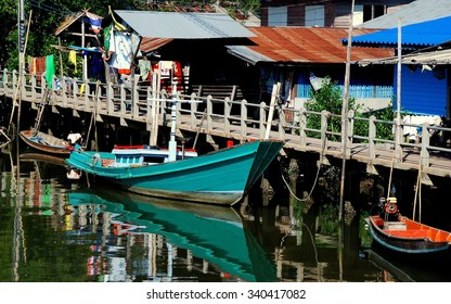 Samut Songkhram, Thailand - December 29, 2011:  Green wooden fishing boat moored to a walkway dock in front of old Thai homes with corrugated metal roofs