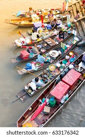 SAMUT SONGKHRAM, THAILAND - MAY 2, 2017: Amphawa floating market with wooden boats busy ferrying people. A traditional popular method of buying and selling still practiced in canals, Thailand.