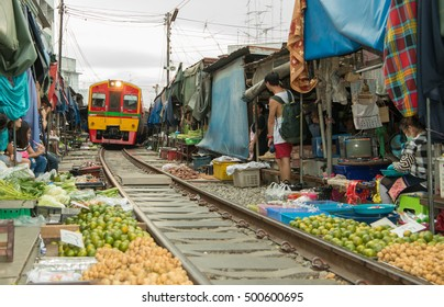 SAMUT SONGKHRAM, THAILAND- - October 18, 2016 : Mae Klong Market placed all product on railroad, all vendors have to move product Train passing the famous market of maeklong in Thailand