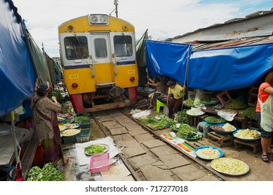 SAMUT SONGKRAM, THAILAND - MAY 23, 2009: Train passes by the Mae Klong railway tracks market in Samut Songkram, Thailand. This market is famous for its location on active railroad line.