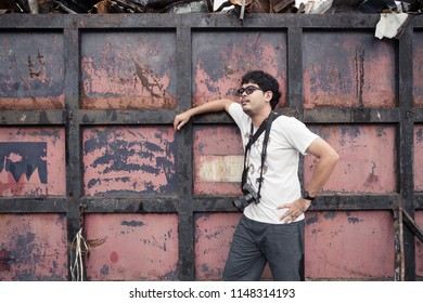 Samutprakan, Thailand - July 28 2018: Man as a mature journal photographer get in huge junk yard in Samutprakan province, Thailand for exploration and observation about environmental and ecology.
