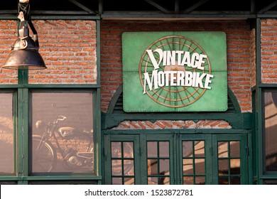 "Samutprakarn, Thailand - Oct 25, 2015: Vintage motorcycle shop sign ""Vintage Motorbike"", big green label attached in front of the shop made of bricks and a vintage motorcycle parked inside the garage"