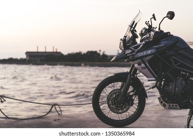 Samutprakran, Thailand - March 11, 2019 : triumph motorcycle new model 2018 triumph tiger xca on the road to beautiful sunset beach.