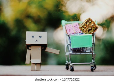 SAMUTSONGKHRAM, THAILAND - DECEMBER 03, 2018: Danbo or Danboard  and toy shopping cart with small gift box on old wood table