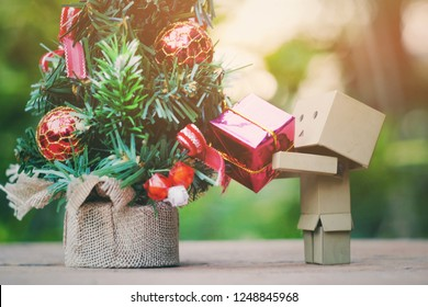 SAMUTSONGKHRAM, THAILAND - DECEMBER 03, 2018: Danbo or Danboard holding small gift box and toy pine tree on old wood table