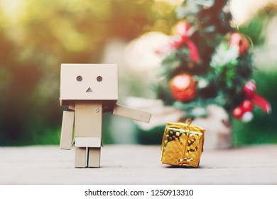 SAMUTSONGKHRAM, THAILAND - DECEMBER 03, 2018: Danbo or Danboard and small gift box on old wood table, merry christmas