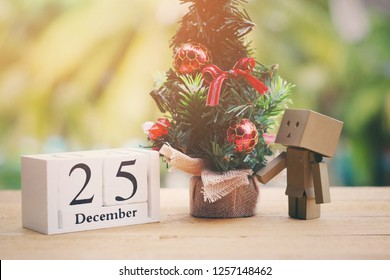 SAMUTSONGKHRAM, THAILAND - DECEMBER 13, 2018: Danbo or danboard standing on wood table with wooden calendar and toy christmas tree