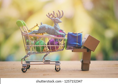 SAMUTSONGKHRAM, THAILAND - DECEMBER 13, 2018: Danbo or danboard holding small gift box and toy shopping cart on old wood table
