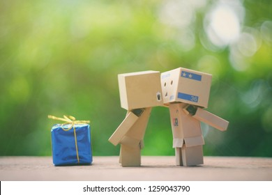 SAMUTSONGKHRAM, THAILAND - DECEMBER 16, 2018: Danbo kissing with love and standing on old wood table
