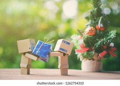 SAMUTSONGKHRAM, THAILAND - DECEMBER 16, 2018: Danbo or Danboard holding small gift box with toy christmas tree background