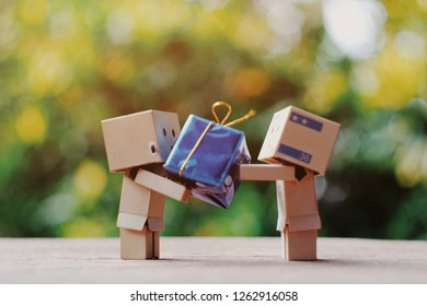 SAMUTSONGKHRAM, THAILAND - DECEMBER 16, 2018: Danbo or Danboard standing on old wood table and holding small gift box, holiday season